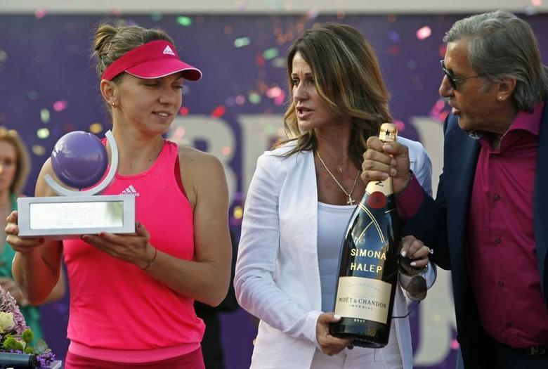 Romanian former gymnast Nadia Comaneci (C) and former tennis player Ilie Nastase offer a champagne bottle to compatriot Simona Halep as she holds the trophy of the BRD Bucharest Open international tennis tournament after defeating Roberta Vinci of Italy in their women's singles final match in Bucharest July 13, 2014. REUTERS/Bogdan Cristel