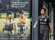 A man walks past a World Cup anti-gambling advertisement at a taxi stand in Singapore July 9, 2014. REUTERS/Edgar Su