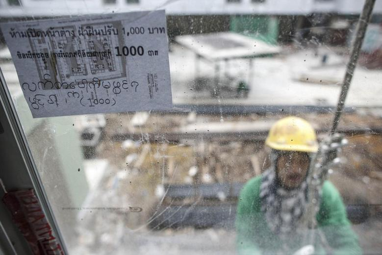 A multi-language sign, written the Thai, Cambodian and Myanmar languages, is seen as a construction labourer works at a building site in Bangkok June 18, 2014. REUTERS/Athit Perawongmetha