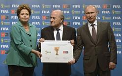El presidente de Rusia, Vladimir Putín (D), la presidenta de Brasil, Dilma Roussef (I), y el presidente de la FIFA, Sepp Blatter (C), en la ceremonia oficial de la entrega de la Copa del Mundo 2018, en Rio de Janeiro, 13 de julio de 2014. La presidenta brasileña, Dilma Rousseff, hizo el domingo la entrega simbólica del Mundial a Rusia, que será anfitrión de la próxima Copa en el 2018. REUTERS/Alexey Nikolsky/RIA Novosti/Kremlin
