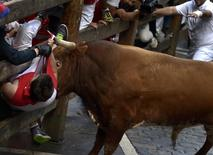 A runner is gored by a Miura fighting bull at Estafeta corner during the eighth running of the bulls of the San Fermin festival in Pamplona July 14, 2014. REUTERS/Vincent West