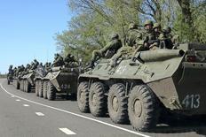 7月14日、NATOは、ロシア軍がウクライナとの国境付近で部隊を増強し、1万人以上を集結させていると明らかにした。写真は国境近くを走行するロシア軍の車両。4月撮影(2014年 ロイター/Alexander Mikhailov)