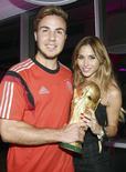 """El alemán Mario Goetze y su novia Ann-Kathrin Broemmel posan con el trofeo de la Copa del Mundo, 13 de julio de 2014. El Mundial de fútbol de Brasil fue el mayor evento jamás visto en las redes sociales con 350 millones de usuarios de Facebook Inc, dijo el lunes la compañía, afirmándose en el mercado de """"tiempo real"""" dominado durante mucho tiempo por Twitter.REUTERS/Markus Gilliar/Pool"""