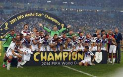 Germany's players pose for pictures as they celebrate with their World Cup trophy after winning their 2014 World Cup final against Argentina at the Maracana stadium in Rio de Janeiro July 13, 2014. REUTERS/Michael Dalder