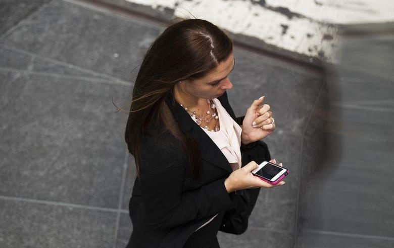 A woman uses her Apple iPhone while walking through Times Square in New York, September 20, 2012.  REUTERS/Lucas Jackson