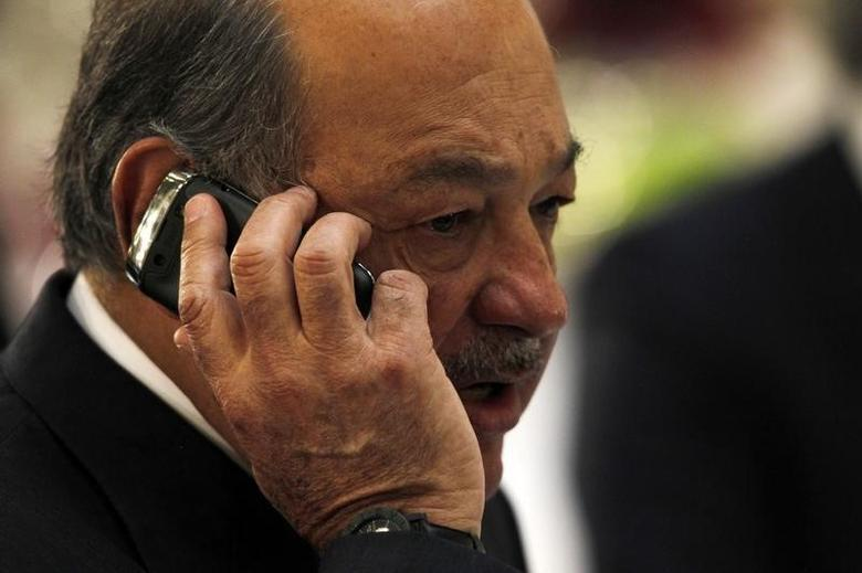 Mexican billionaire Carlos Slim speaks on his mobile phone during an official visit by Portugal's Prime Minister Pedro Passos Coelho at the National Palace in Mexico City October 16, 2013. REUTERS/Edgard Garrido