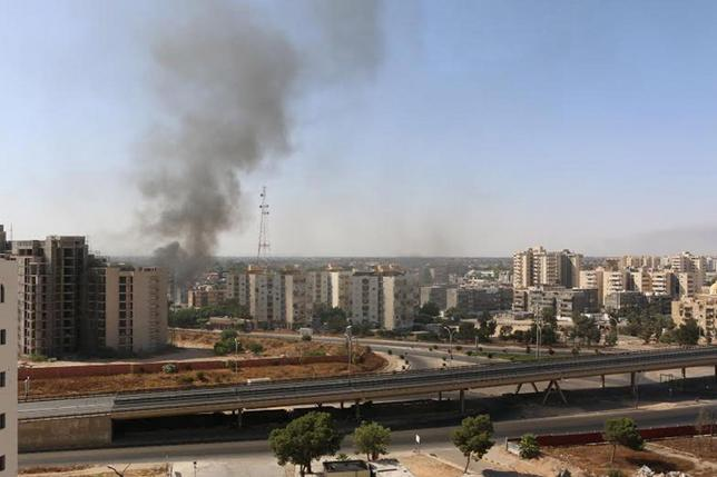 Smoke rises near buildings after heavy fighting between rival militias broke out near the airport in Tripoli July 13, 2014.   REUTERS/ Hani Amara
