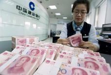 Сотрудник отделения China Construction Bank считает юани в Хайане, 10 июня 2014 года. Прямые иностранные инвестиции в Китай выросли на 2,2 процента в годовом исчислении в первой половине 2014 года и лишь слегка - в июне, указывая на осторожный оптимизм инвесторов в отношении состояния второй по величине экономики мира. REUTERS/China Daily