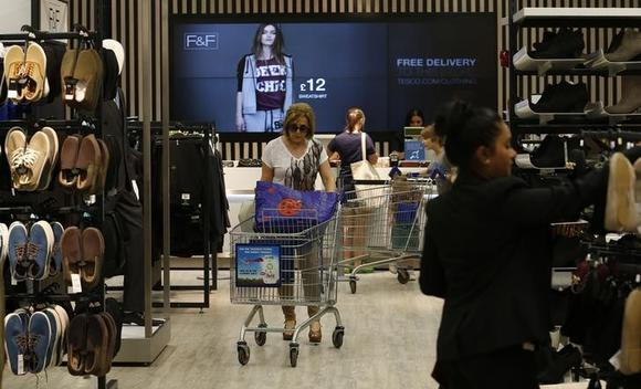 Customers shop in the F&F clothing department at a Tesco Extra supermarket in Watford, north of London August 8, 2013.  REUTERS/Suzanne Plunkett