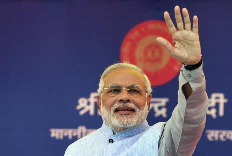 Indian Prime Minister Narendra Modi waves to a crowd at a gathering after inaugurating a train on a new stretch of railway to the town of Katra, northwest of Jammu July 4, 2014.  REUTERS/Mukesh Gupta