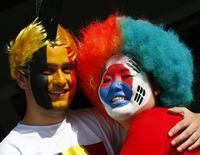 Torcedores da Bélgica  e Coreia do Sul se abraçam antes de partida pelo Grupo H, na Arena Corinthians, em São Paulo. 26/06/2014. REUTERS/Eddie Keogh