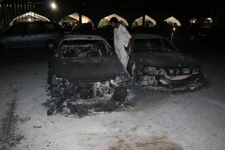 A member of the Zintan city forces inspects burnt cars after a rival militia shelled Tripoli International Airport in Tripoli July 14, 2014.   REUTERS/Hani Amara