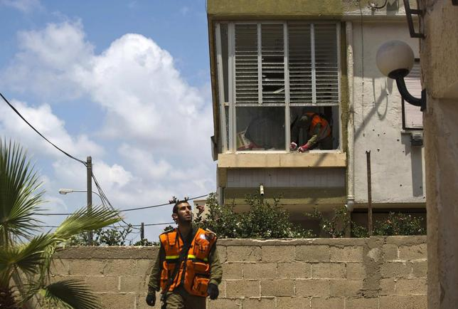 An Israeli soldier clears debris at the scene after a rocket fired by Palestinian militants in Gaza landed in Ashdod July 15, 2014.  REUTERS/Amir Cohen