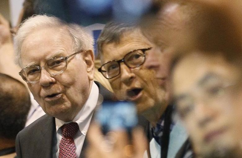 Microsoft founder and technology advisor Bill Gates (C) and his friend Berkshire Hathaway CEO Warren Buffett (L) react during a newspaper throwing competition at a trade show, at the Berkshire Hathaway annual meeting in Omaha, Nebraska May 3, 2014. REUTERS/Rick Wilking/Files