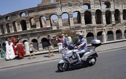 Matteo Achilli passa pelo Coliseu de Roma dirigindo sua moto. 25/7/2013. REUTERS/Tony Gentile