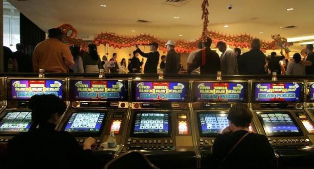 Gamblers continue playing slots as members of the Lohan School of Shaolin perform a dragon dance to celebrate Chinese New Year in the casino of the Las Vegas Hilton, Nevada February 9, 2008.  REUTERS/Las Vegas Sun/Sam Morris