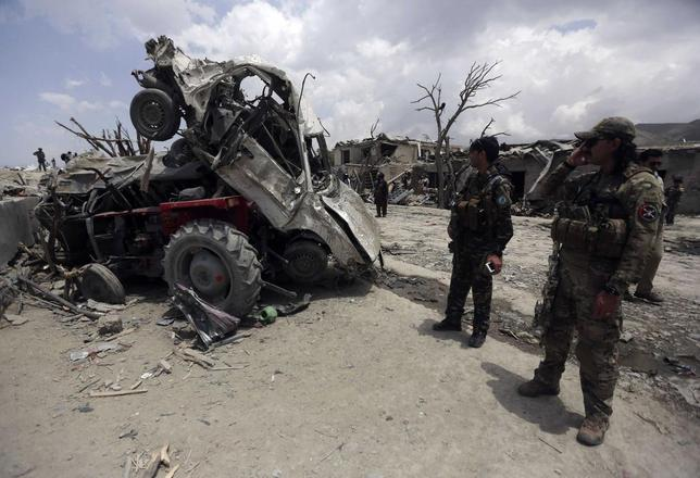 Afghan security forces inspect at the site of yesterday's car bomb attack on a market in Urgon district, Paktika province, July 16, 2014. REUTERS/Omar Sobhani