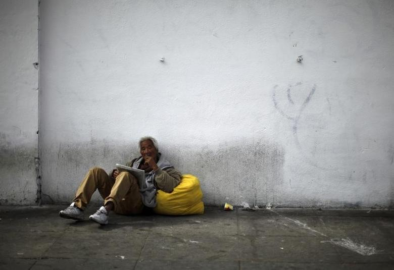 A man sits on downtown Los Angeles' Skid Row, March 6, 2013. REUTERS/Lucy Nicholson