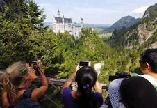 Tourists take pictures at the south Bavarian Neuschwanstein castle near Schwangau, about 120 km (74 miles) south of Munich, August 15, 2013.  REUTERS/Michael Dalder