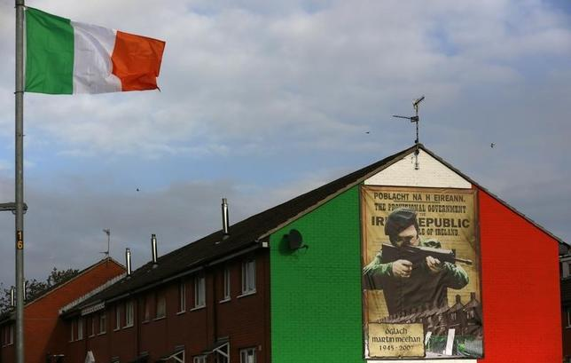 An Irish flag flies beside a mural in the Ardoyne area of North Belfast displaying an image of a I.R.A. gunman November 5, 2013. REUTERS/Cathal McNaughton