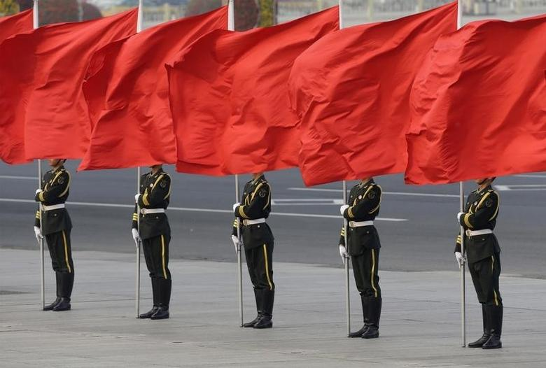 Members of honour guards hold red flags during a welcoming ceremony for Denmark's Queen Margrethe II outside the Great Hall of the People in Beijing April 24, 2014. REUTERS/Jason Lee