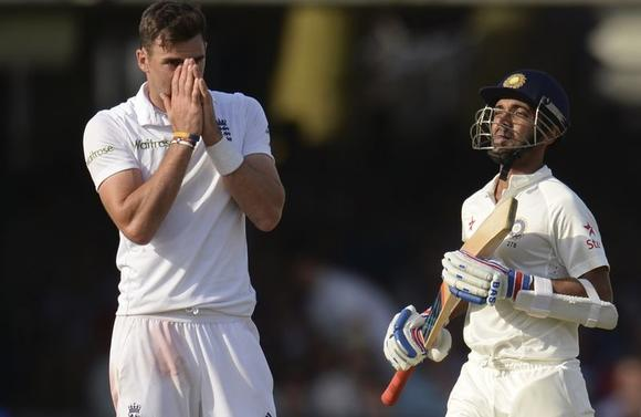 England's James Anderson reacts as India's Ajinkya Rahane (R) collects more runs during the second cricket test match at Lord's cricket ground in London July 17, 2014. REUTERS/Philip Brown
