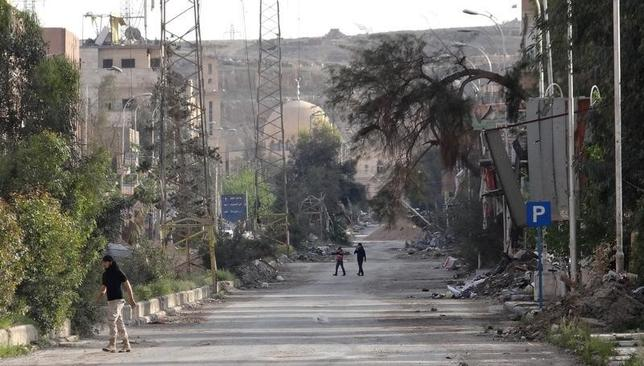 People walk along a damaged street in Deir al-Zor, eastern Syria April 3, 2014. Picture taken April 3, 2014. REUTERS/Mohamed al-Khalif