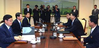 Kwon Kyung-sang (2nd L), secretary general of the Incheon Asian Games Organizing Committee, meets with Vice Chairman of North Korean Olympic Committee Son Kwang Ho (2nd R) during their talks on the North's participation in the Asia Games, at the Peace House on the southern side of the truce village of Panmunjom in the demilitarised zone separating the two Koreas, in this picture provided by Unification Ministry and released by Yonhap on July 17, 2014.  REUTERS/Unification Ministry/Yonhap