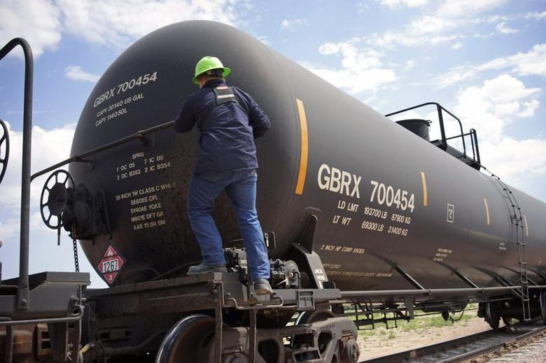 A worker climbs onto a crude oil train to set the handbrake at the Eighty-Eight Oil LLC's transloading facility in Ft. Laramie, Wyoming July 15, 2014.  REUTERS/Rick Wilking