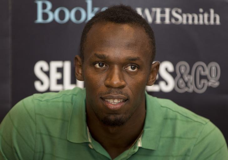 Jamaican athlete Usain Bolt poses for photographers as he signs copies of his autobiography, ''Faster than Lightning,''  at Selfridges in central London September 19, 2013. REUTERS/Neil Hall