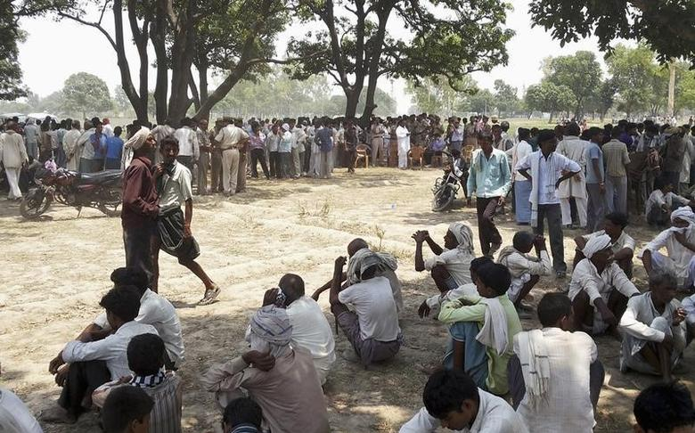 Onlookers sit at the site where two girls were hanged from a tree at Badaun district in the northern Indian state of Uttar Pradesh May 28, 2014. REUTERS/Stringer