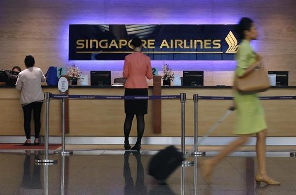 People walk past a Singapore Airlines ticketing counter at Changi Airport in Singapore May 7, 2014. REUTERS/Edgar Su/Files