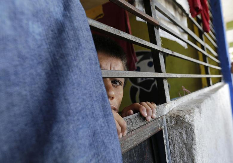 A youth looks through a barred window inside a home known as ''La Gran Familia'' (The Big Family), in the western city of Zamora July 17, 2014. REUTERS/Henry Romero