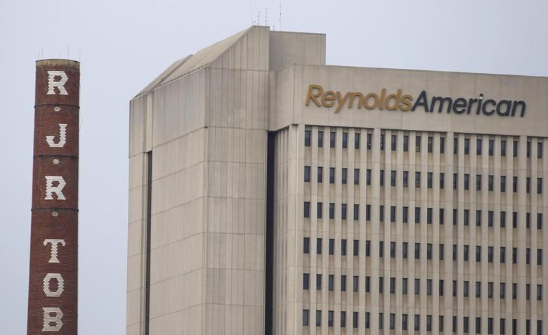 The headquarters of Reynolds American is seen next to the old R.J. Reynolds Tobacco smoke stacks from a previous manufacturing plant in downtown Winston-Salem, North Carolina May 23, 2014.  REUTERS/Chris Keane