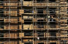 Two construction workers are shown standing on scaffolding at an apartment building under construction in Hollywood, California November 12, 2009. REUTERS/Fred Prouser