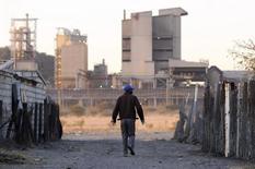 A township resident walks past Lonmin's Marikana platinum mine, June 13, 2014. REUTERS/Skyler Reid