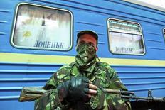 Вооруженный пророссийский сепаратист на ж/д вокзале в Донецке 21 июля 2014 года. Несмотря на резкие заявления Европы, России вряд ли грозит более серьезное наказание за сбитый над территорией Украины самолет, чем ускорение применения уже согласованных индивидуальных санкций. REUTERS/Konstantin Cherginsky