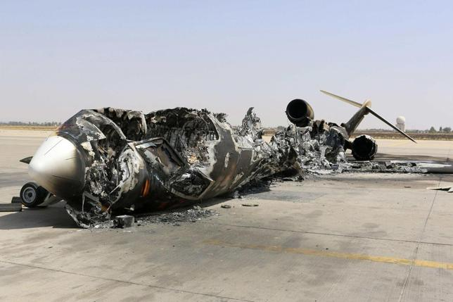 A wreckage of a burnt aircraft is pictured after a shelling at Tripoli International Airport July 21, 2014. Heavy fighting erupted on Sunday around Tripoli International Airport, where rival militias have been battling for control, killing at least four people and forcing thousands from their homes, local residents and witnesses said. REUTERS/Hani Amara