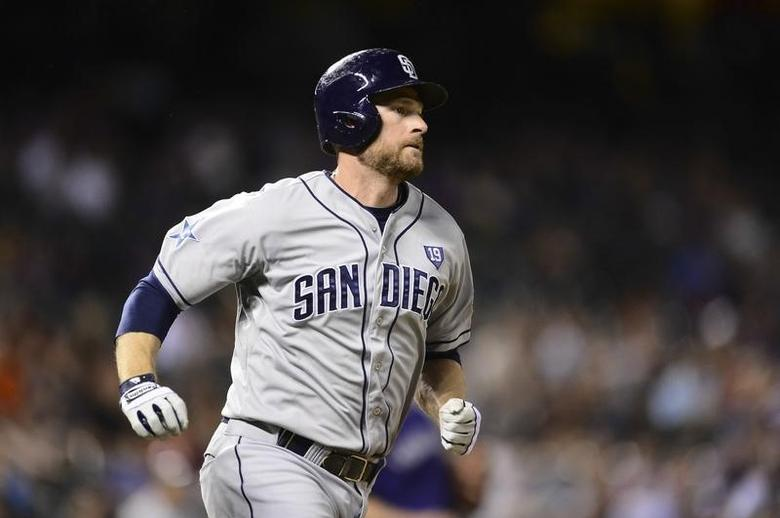 San Diego Padres third baseman Chase Headley (7) runs after hitting a RBI triple in the seventh inning against the Colorado Rockies at Coors Field.Jul 7, 2014; Denver, CO, USA; Ron Chenoy-USA TODAY Sports
