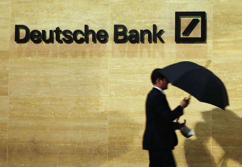 A man walks past Deutsche Bank offices in London December 5, 2013. REUTERS/Luke MacGregor
