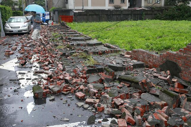 A man walks over fallen bricks from a wall that was blown over by strong winds from Typhoon Matmo which hit Taiwan, in Taipei July 23, 2014. REUTERS/Pichi Chuang