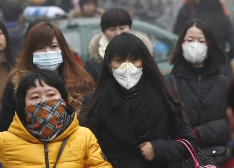 Commuters wearing masks make their way amid thick haze in the morning in Beijing February 26, 2014. REUTERS/Kim Kyung-Hoon/Files