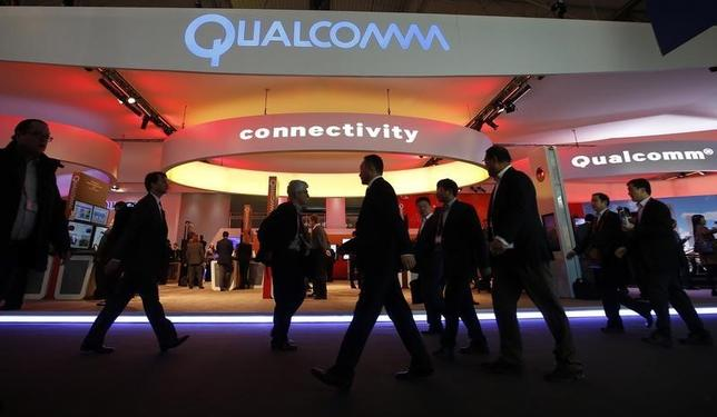 Visitors walk past the Qualcomm stand at the Mobile World Congress in Barcelona, February 24, 2014. REUTERS/Albert Gea/Files