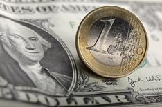 Долларовая банкнота и монета евро в Варшаве 18 января 2011 года. Курс евро близок к минимуму восьми месяцев накануне выхода индекса PMI еврозоны за июль. REUTERS/Kacper Pempel