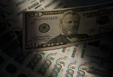 Банкноты российского рубля и доллара США в Москве 17 февраля 2014 года. Рубль дешевеет утром четверга из-за рисков объявления Евросоюзом уже сегодня новых санкций против России, часть из которых может носить экономический характер. REUTERS/Maxim Shemetov