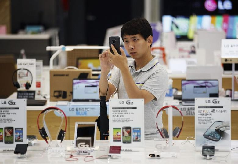 A customer tries out an LG electronics' smart phone at a store in Seoul July 22, 2014. REUTERS/Kim Hong-Ji