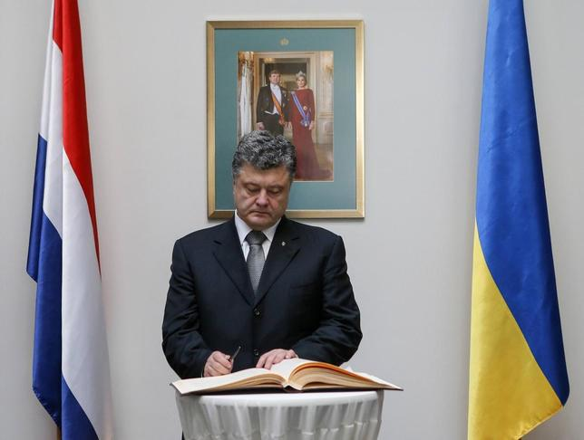 Ukraine's President Petro Poroshenko, standing under a framed photo of Dutch King Willem-Alexander and his wife Queen Maxima, signs a book of condolence as he commemorates victims of Malaysia Airlines Flight MH17 at the Dutch embassy in Kiev July 21, 2014. REUTERS/Sergey Dolzhenko/Pool