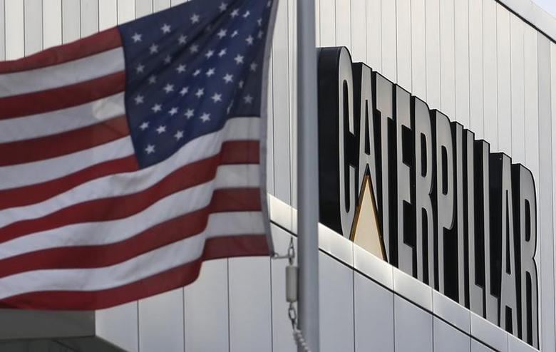 The Caterpillar Visitors Center is seen behind the U.S. national flag in Peoria, Illinois, in this file photo taken November 26, 2013.   REUTERS/Jim Young/Files
