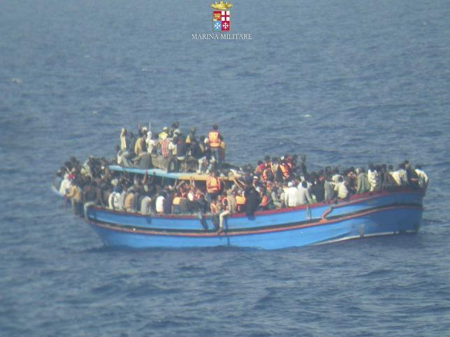 Migrants sit in their boat during a rescue operation by Italian navy ship Grecale (not pictured) off the coast of Sicily, in this handout picture by the Italian Marina Militare June 29, 2014. Around 30 migrants were found dead on another boat packed with people off the coast of Sicily, said Italy's navy which rescued thousands more trying to leave North Africa over the weekend. REUTERS/Marina Militare/Handout via Reuters