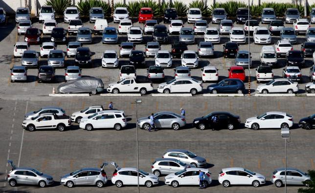 Workers check new cars before they are transported to dealers in Sao Bernardo do Campo April 29, 2014. REUTERS/Paulo Whitaker